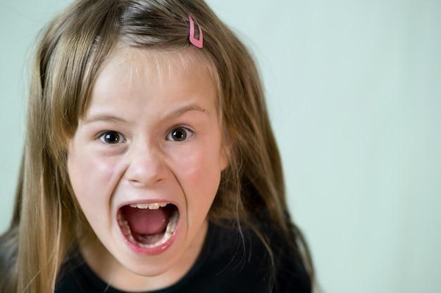 Bouchent portrait de fille enfant criant en colère regardant agressivement à huis clos.