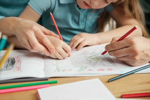 Bouchent le portrait d'une fille peignant un arbre de noël avec ses parents. père, mère et leur fille passent du temps ensemble. une journée en famille.