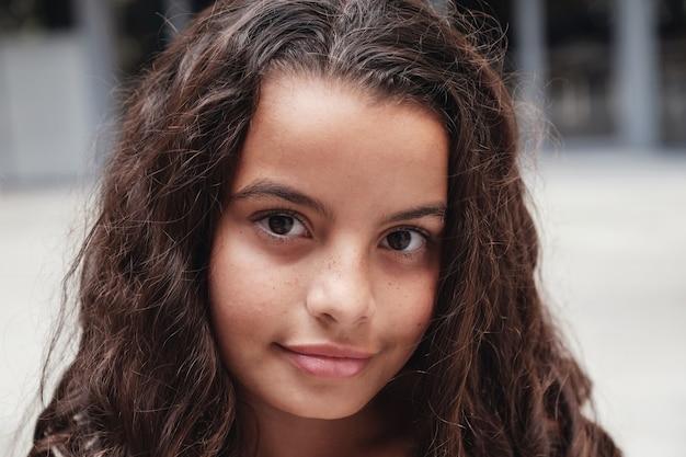 Bouchent le portrait d'une fille préteen multiculturelle mélangée confiante, charmante et magnifique avec de beaux cheveux bouclés.