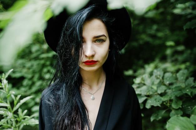 Bouchent le portrait d'une fille sensuelle tout en noir, des lèvres rouges et un chapeau. goth femme dramatique.