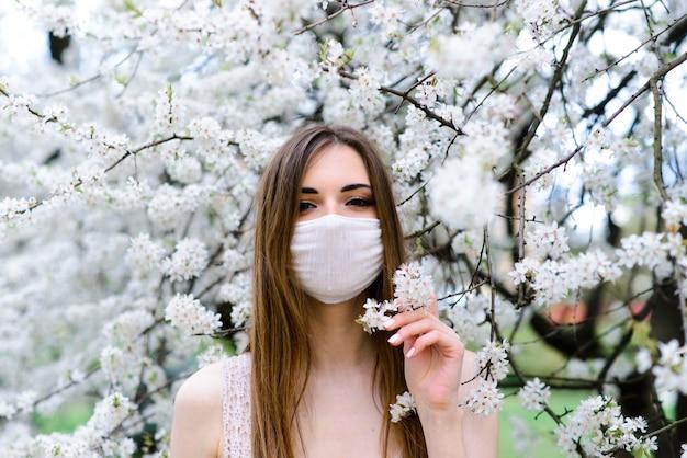 Bouchent le portrait d'une fille tendre dans un chemisier blanc sous un cerisier en fleurs avec un masque avec des fleurs sur du coronavirus.