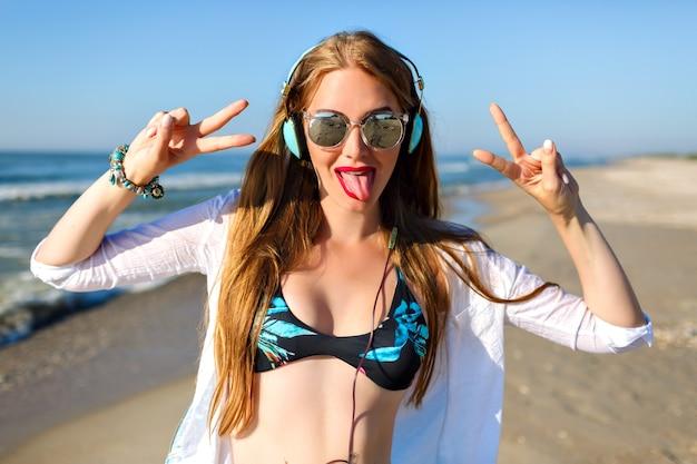 Bouchent le portrait fou de jolie jeune femme drôle, écoutant de la musique sur ses écouteurs, haut de bikini floral lumineux, longs cheveux blonds et t-shirt blanc.