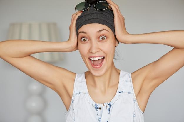 Bouchent le portrait de l'heureuse belle jeune femme en bandeau gris à la recherche d'excité