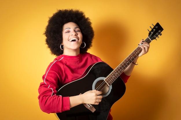 Bouchent le portrait de l'heureuse jeune femme afro-américaine en riant avec guitare
