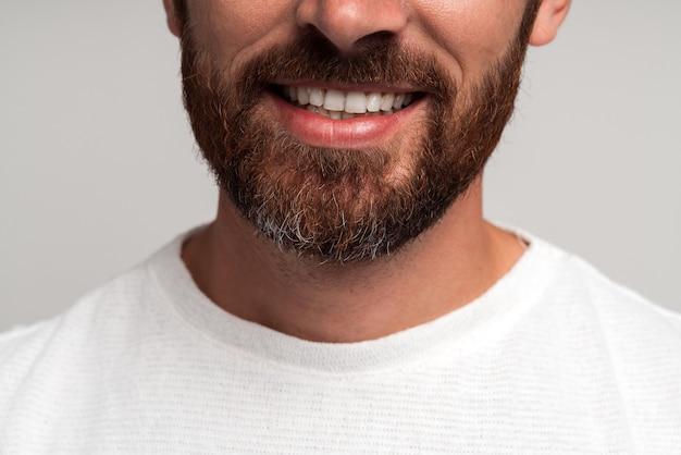Bouchent le portrait de l'heureux bel homme d'affaires barbu debout et souriant. studio intérieur tourné, isolé sur fond gris clair