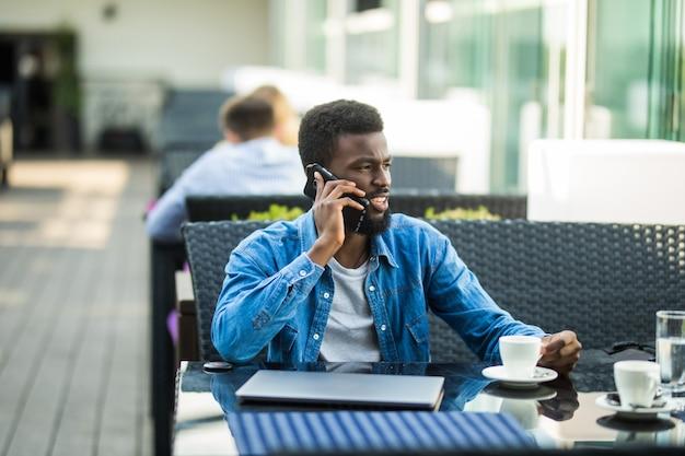 Bouchent le portrait d'heureux homme afro-américain assis au café avec téléphone mobile