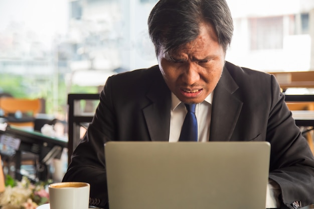 Bouchent portrait homme d'affaires asiatique moyen-âge sérieux à l'aide d'un ordinateur portable avec une tasse de café à côté au bureau moderne.