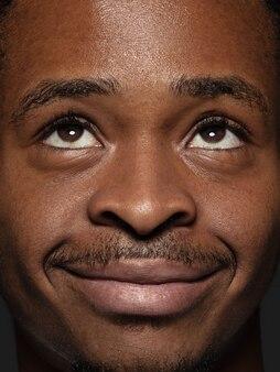 Bouchent le portrait d'un homme afro-américain jeune et émotionnel. photo très détaillée d'un modèle masculin avec une peau bien entretenue et une expression faciale brillante. concept d'émotions humaines. levant les yeux et sourire.