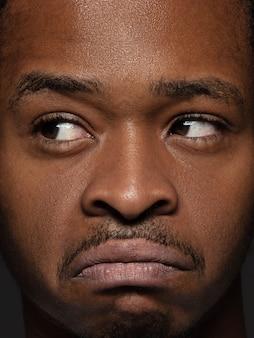 Bouchent le portrait d'un homme afro-américain jeune et émotionnel. photo très détaillée d'un modèle masculin avec une peau bien entretenue et une expression faciale brillante. concept d'émotions humaines. réfléchi.