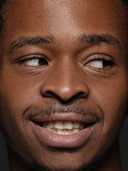 Bouchent le portrait d'un homme afro-américain jeune et émotionnel. photo très détaillée d'un modèle masculin avec une peau bien entretenue et une expression faciale brillante. concept d'émotions humaines. regardant de côté.
