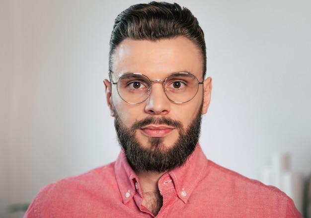 Bouchent Le Portrait D'un Homme Barbu Attrayant, élégance Et Confiant à Lunettes Et Chemise à La Maison Tout En Regardant La Caméra Photo Premium