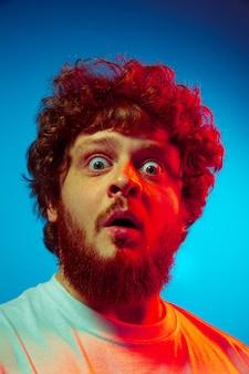 Bouchent le portrait de l'homme isolé sur le mur bleu du studio en néon rouge