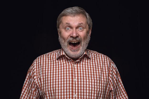 Bouchent le portrait d'un homme senior isolé sur fond noir de studio. photoshot des émotions réelles du modèle masculin. vous vous demandez, passionnant et étonné. expression faciale, concept d'émotions humaines.