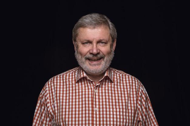 Bouchent le portrait d'un homme senior isolé sur fond noir de studio. sourire, se sentir heureux.