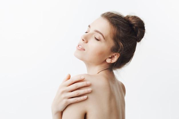 Bouchent portrait isolé de la belle jeune femme brune avec une coiffure chignon touchant l'épaule avec la main, ayant une expression détendue et calme avec les yeux fermés.