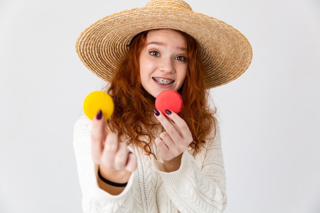 Bouchent le portrait d'une jeune adolescente joyeuse portant chapeau d'été debout isolé sur fond blanc, tenant des macarons