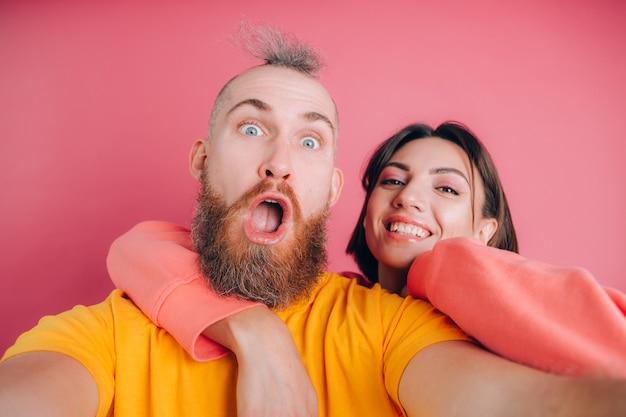 Bouchent le portrait de jeune, caucasien, attrayant, charmant, mignon, doux, souriant, couple positif en casual faisant selfie sur téléphone mobile sur fond rose