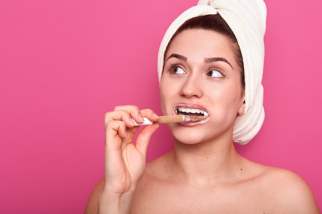 Bouchent portrait de jeune femme adorable se brosser les dents, portant une serviette blanche