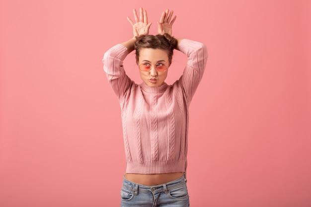 Bouchent le portrait de jeune femme assez mignonne avec l'expression du visage drôle en pull rose et lunettes de soleil isolé sur fond rose de studio, duper