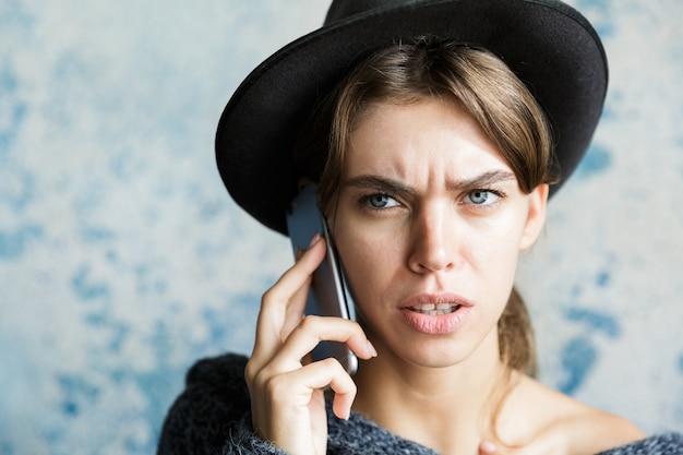 Bouchent le portrait d'une jeune femme confuse habillée en chapeau et pull parler au téléphone mobile sur mur bleu