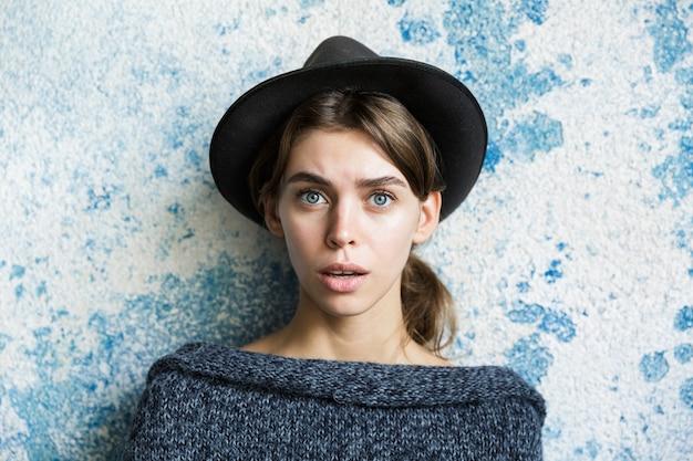Bouchent le portrait d'une jeune femme confuse habillée en pull et chapeau sur mur bleu