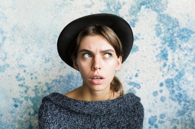 Bouchent le portrait d'une jeune femme confuse vêtue d'un pull et d'un chapeau sur un mur bleu, à l'écart