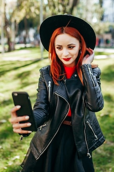Bouchent le portrait d'une jeune femme élégante tenant un smartphone