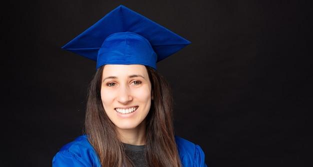 Bouchent le portrait de jeune femme étudiante gaie portant un bonnet de graduation