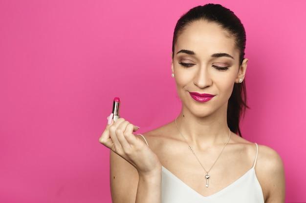 Bouchent le portrait d'une jeune femme sur fond rose.
