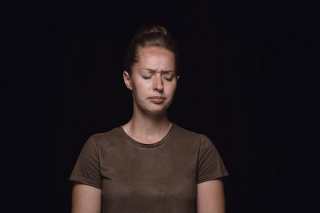Bouchent le portrait de jeune femme isolée sur le mur noir du studio