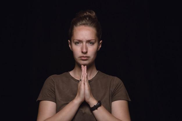 Bouchent le portrait de jeune femme isolée sur mur noir