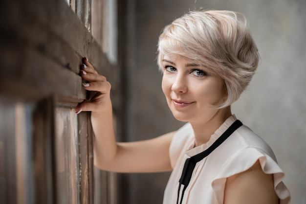 Bouchent le portrait de jeune femme jolie blonde aux yeux bleus debout près de la fenêtre à la lumière naturelle