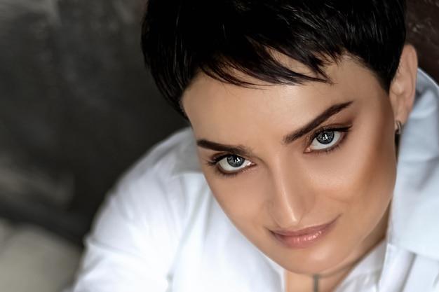 Bouchent le portrait de jeune femme jolie brune aux yeux bleus