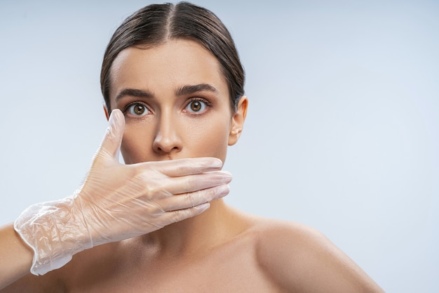 Bouchent le portrait d'une jeune femme joyeuse mettant la main dans des gants sur sa bouche