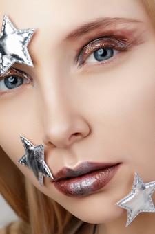 Bouchent le portrait de jeune femme avec maquillage créatif. verre liquide, paillettes métalliques et yeux smokey modernes.