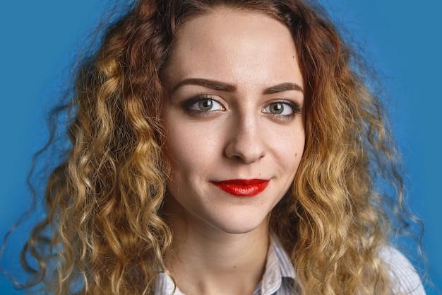 Bouchent le portrait d'une jeune femme à la recherche amicale heureuse avec des cheveux ondulés volumineux et des lèvres rouges se détendre à l'intérieur contre le mur de mur bleu, ayant une expression positive joyeuse sur son joli visage