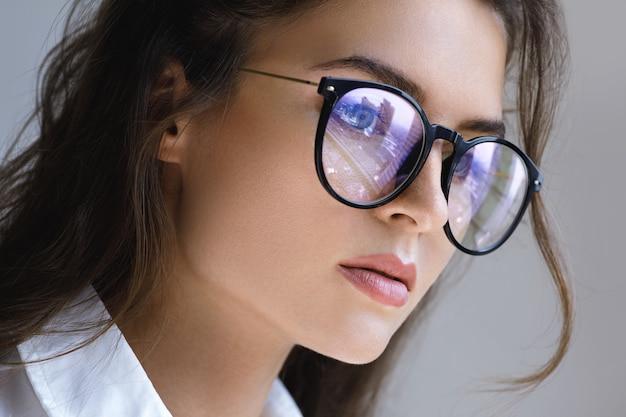 Bouchent portrait de jeune femme avec un reflet de la ville moderne à l'intérieur des lunettes