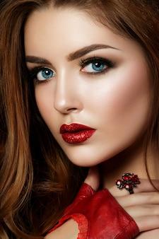 Bouchent le portrait de jeune femme rousse portant des lèvres rouges avec des paillettes et des yeux charbonneux bruns. des sourcils parfaits. maquillage de mode moderne.