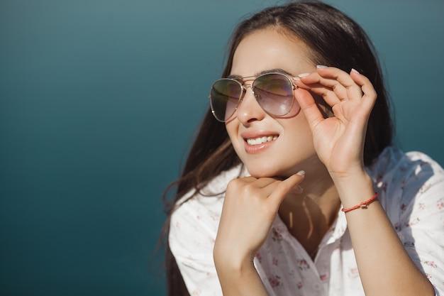 Bouchent le portrait de jeune femme séduisante portant des lunettes de soleil