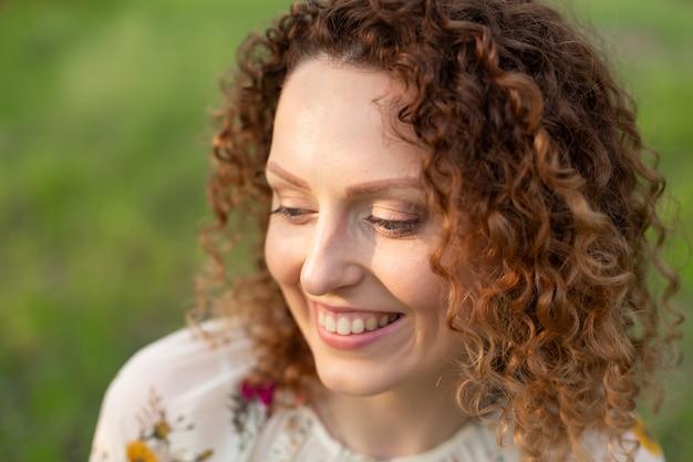 Bouchent le portrait de jeune femme séduisante souriante aux cheveux bouclés dans le parc de printemps de floraison verte. émotions pures.