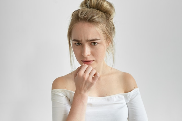 Bouchent le portrait d'une jeune femme sérieuse déçue avec des taches de rousseur fronçant les sourcils, ayant un regard concentré tendu, touchant ses lèvres tout en réfléchissant à un problème. émotions, sentiments et réactions humaines