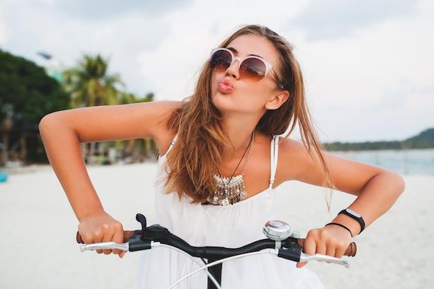 Bouchent le portrait de jeune femme souriante en robe blanche à cheval sur la plage tropicale sur des lunettes de soleil de vélo voyageant en vacances d'été en thaïlande