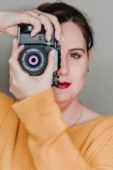 Bouchent le portrait d'une jeune femme tenant un appareil photo. concept de photographie