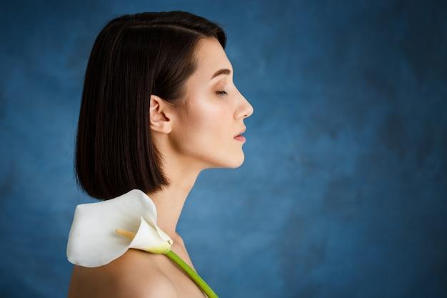 Bouchent portrait de jeune femme tendre avec fleur blanche sur mur bleu