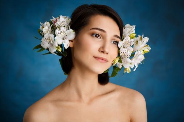 Bouchent portrait de jeune femme tendre avec des fleurs blanches sur le mur bleu