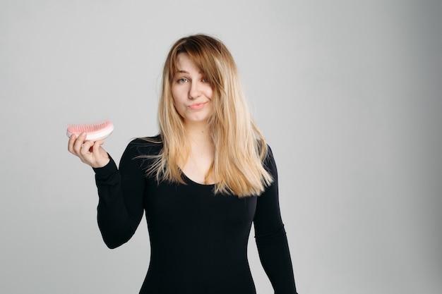 Bouchent portrait de jeune fille confuse aux cheveux blonds en désordre