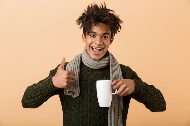 Bouchent le portrait d'un jeune homme africain heureux habillé en vêtements d'automne isolé sur un mur beige, tenant une tasse, montrant les pouces vers le haut
