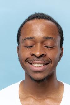 Bouchent le portrait de jeune homme afro-américain en chemise blanche sur l'espace bleu