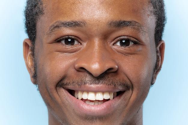Bouchent le portrait de jeune homme afro-américain en chemise blanche sur le mur bleu. émotions humaines, expression faciale, publicité, concept de vente. il a l'air heureux, souriant. sensation agréable.