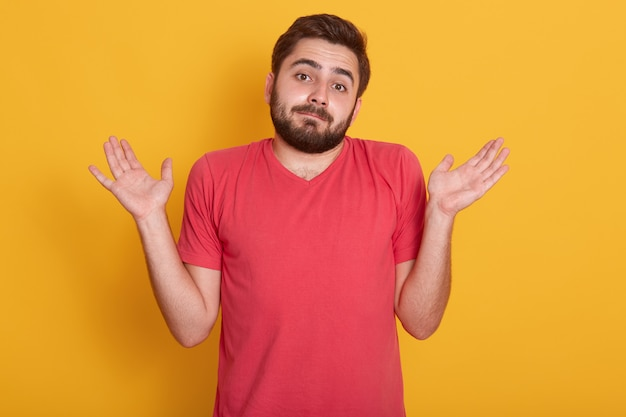 Bouchent portrait de jeune homme étonné en t-shirt décontracté rouge posant isolé sur jaune